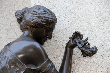 Grieving woman with flowers  sculpture  photo