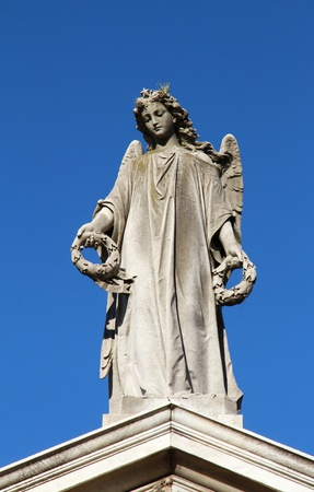 Angel with wreaths in hands female statue  Grief and memory