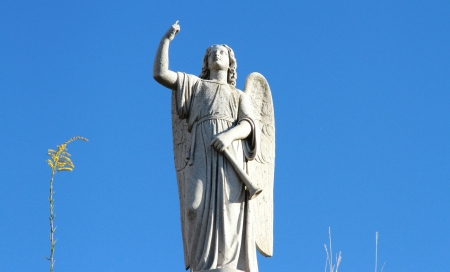 Guardian angel stone statue against the blue sky