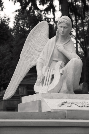 Angel with a harp. A sculpture at the cemetery.
