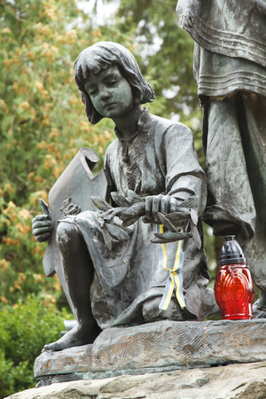 Girls sculpture and candle of memory. Lychakovsky cemetery, Lviv.