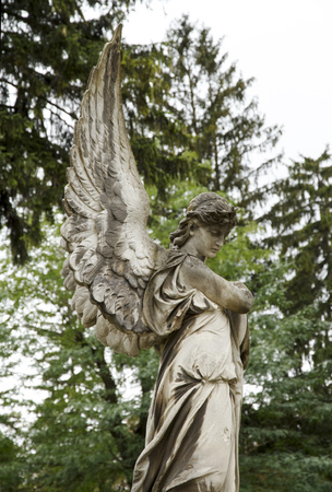 Angel woman old sculpture at a grave. Lychakovsky cemetery, Lviv. Stock Photo