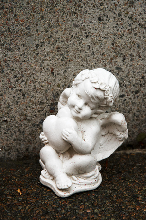 Little angel with heart figure on a grave. Memory of darlings. Stock Photo
