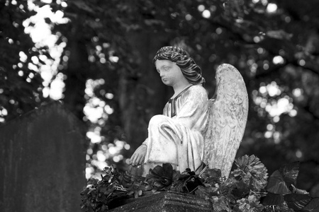 Angel sitting on an old grave. Imperishable memory.