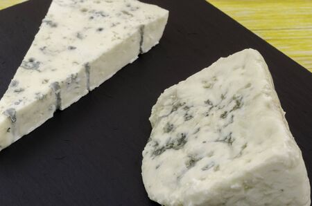 roquefort: Roquefort and gornozola over slate plate and wood. Stock Photo
