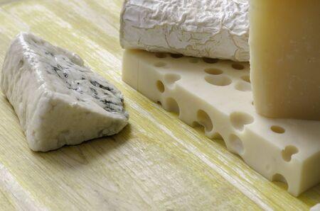 gruyere: Spanish Manchego cheese gruyere goat gorgonzola over yellow wood. Stock Photo