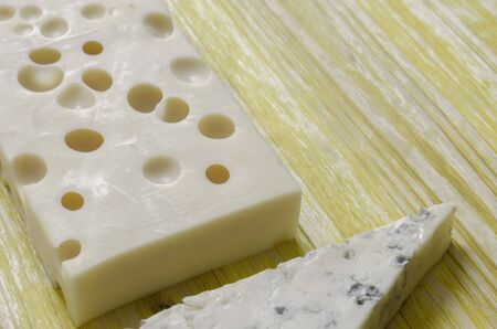 gruyere: Gorgonzola and gruyere cheese over yellow wood. Stock Photo