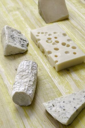 gruyere: Spanish Manchego cheese gruyere goat gorgonzola over yellow wood. Stock Photo