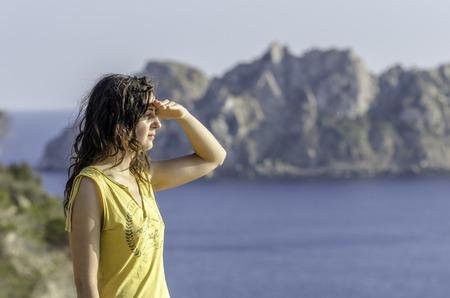 mujer mirando el horizonte: Hermosa mujer mirando hacia el futuro con la mano en la frente y el mar de fondo Foto de archivo