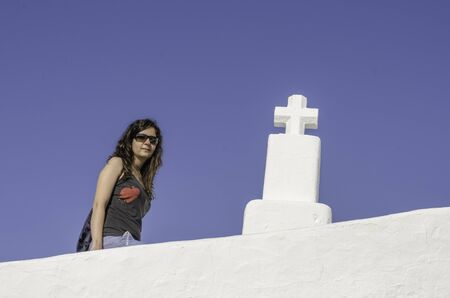 brunets: Girl with sunglasses and cross with blue background, Ibiza. Stock Photo