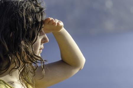 Mooie vrouw kijkt vooruit met de hand in het voorhoofd en de zee op de achtergrond Stockfoto