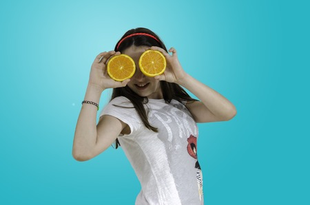 Girl playing with oranges over blue background, teenager. Stock Photo