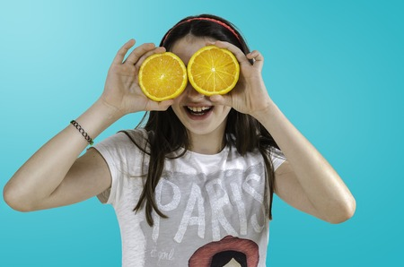 Consumables: Girl with oranges in her eyes blue background, teenager.