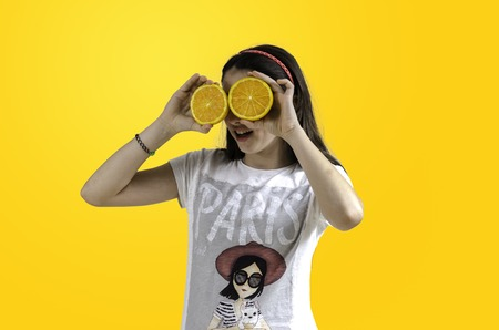 Consumables: Girl with oranges in her eyes yellow background, teenager. Stock Photo
