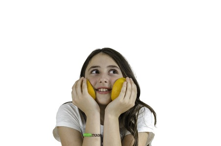 consumables: Girl playing with oranges over white background, teenager. Stock Photo