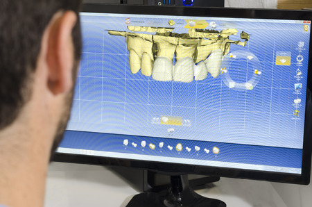 Dental technician, dentist is working with computer. Imagens