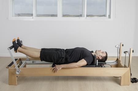 reformer: Man doing pilates in reformer bed, inside.