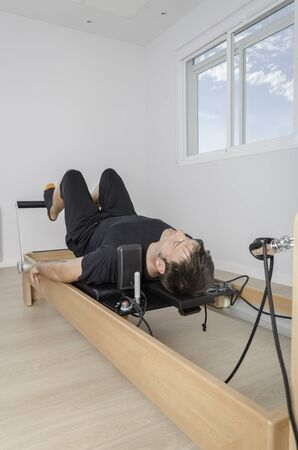 reformer: Man doing exercise of pilates with reformer bed. Stock Photo