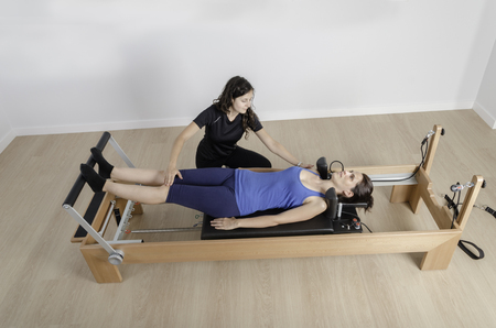 woman doing exercise of pilates with instructor in reformer bed.