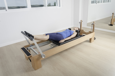 reformer: woman doing exercise of pilates with reformer bed. Stock Photo