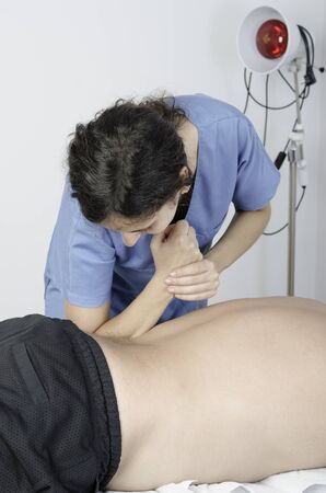 technic: Physiotherapist doing a massage technic with her elbow for deep muscle.