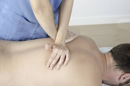 Physiotherapist doing a Dog technique over back spine. Osteopathy.