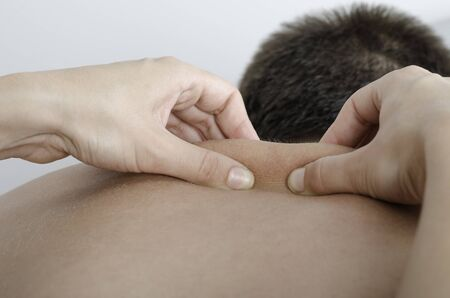 'pull over': Physiotherapist doing a manual testing over dorsal spine, pull and roll. Massage. Stock Photo