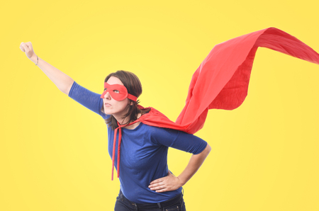 Woman superhero with red cape, yellow background.