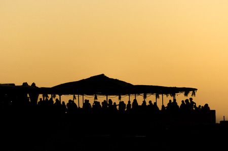 People on a beach party event in sunset. Dancing and partying. Summer electronic music. Silhouette of people.