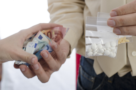 illegal drugs: Closeup of drug trading with euros and pills. Stock Photo