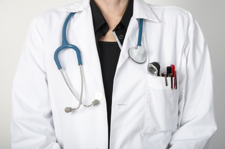 doctors and nurses: Female doctor with a stethoscope at neck, grey background, not face visible Stock Photo