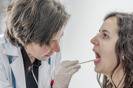 female tongue: Female doctor using a tongue depressor with girl patient Stock Photo
