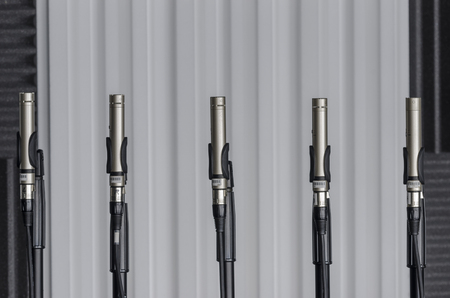 condenser: Condenser microphones placed in microphone stands in a lab of sound. Engineers make innovative sounds