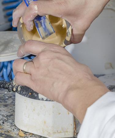 plaster mould: Dental technician is emptying plaster models in her lab.