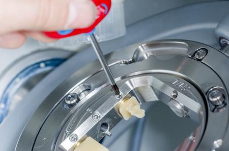 Primo piano di odontotecnico svitare le ceramiche ibride della fresatrice. Archivio Fotografico