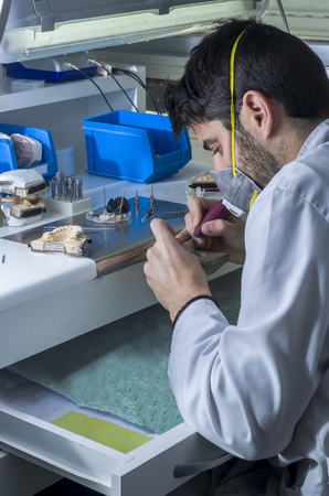 dental laboratory: Dental technician is working with articulator in metal structure of a dental crown or bridge in dental laboratory.