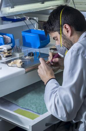 laboratorio dental: T�cnico dental que trabaja con articulador en la estructura met�lica de una corona dental o un puente en el laboratorio dental. Foto de archivo