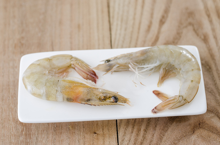 gambas: Raw prawn on white plate on wood background.