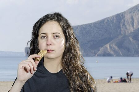energy bar: Woman brunette relaxing after sport and eating a energy bar in a beach. Stock Photo