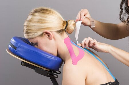 trapezius: Kinesiotaping. Physical therapist applying tape to patient. Pink: cervial, trapezius, supraspinatus, blue: high dorsal paravertebral. Stock Photo