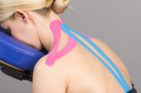 neuromuscular: Kinesiotaping. Physical therapist applying tape to patient. Pink: cervical, trapezius, supraspinatus, blue: high dorsal paravertebral. Stock Photo