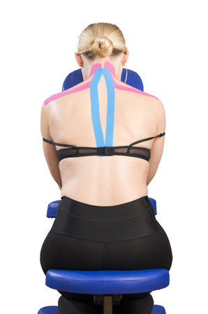 trapezius: Kinesiotaping. Physical therapist applying tape to patient. Pink: cervical, trapezius, supraspinatus, blue: high dorsal paravertebral. Stock Photo