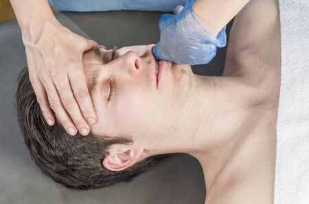 Physiotherapist is doing intraoral technique of massage masseter muscle.