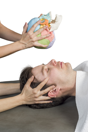 Physiotherapist doing a cranial sacral therapy to a man patient and another physiotherapist with a fake skull showing  position of the hands. Stock Photo