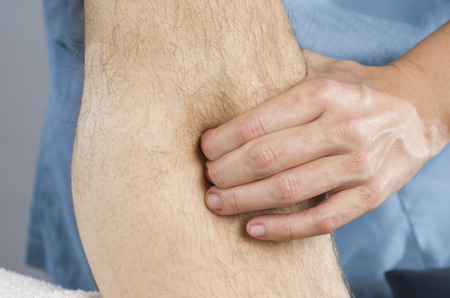 spinal adjustment: Closeup of hands of chiropractor doing calf muscle massage to man patient. Stock Photo