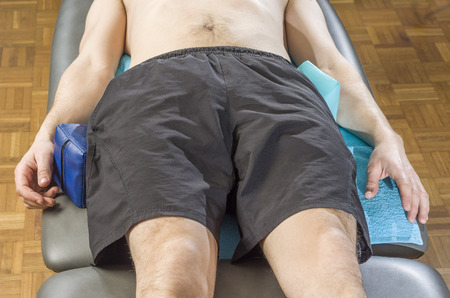 paciente en camilla: paciente de sexo masculino en la camilla con las cu�as de protecci�n postural de sacroil�aca.