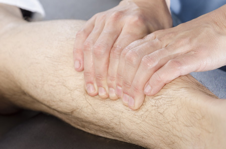 spinal adjustment: Closeup of hands of chiropractorphysiotherapist doing calf muscle massage to man patient.