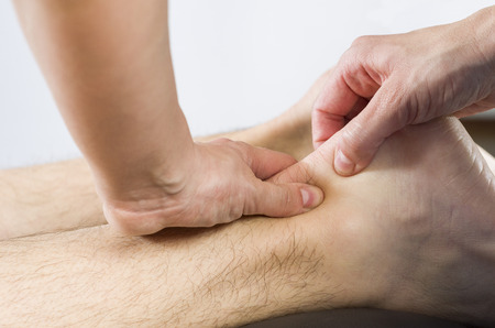 Closeup of hands of chiropractorphysiotherapist doing calf muscle massage to man patient.