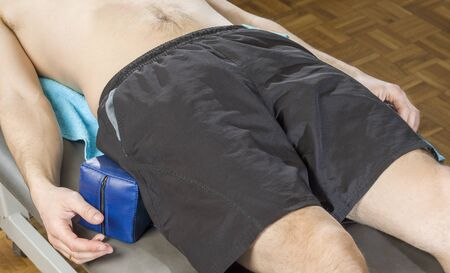 spinal adjustment: Male patient in stretcher with wedges for postural protection of sacroiliac.