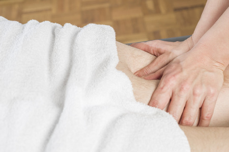 spinal adjustment: physiotherapist doing a hamstrings  massage to man patient. Osteopathy